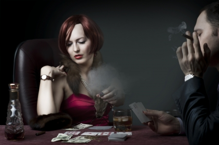 Couple - rich woman and man in suit playing poker, drink whiskey and smoke cigar. Retro style photo