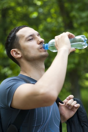 hot water bottle: man drinking water after sport in a park  Stock Photo