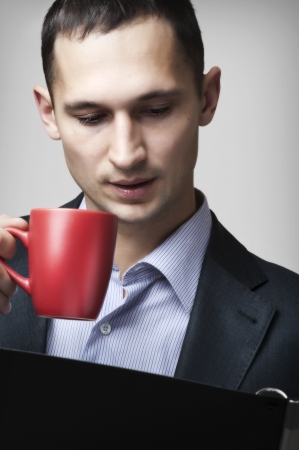 Portrait of a handsome young businessman man reading documents in folder and drinking tea Stock Photo - 13889057