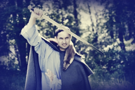 capote: Fantasy portrait of handsome dangerous man with medieval sword Stock Photo