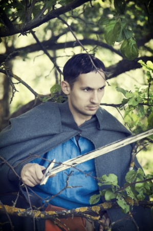 warrior pose: Fantasy portrait of handsome dangerous man with medieval sword Stock Photo