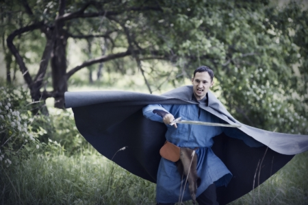 cloak: Fantasy portrait of handsome dangerous man with medieval sword Stock Photo