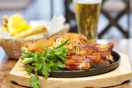 rib: Cerca de la barbacoa costillas de cerdo y verduras. Con el pan y la cerveza en el restaurante