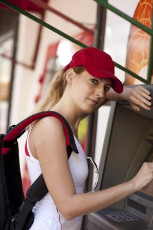 withdraw: A young girl puts your card into an ATM machine