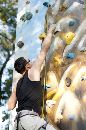 adult wall: Man on artificial exercise climbing wall outdoor