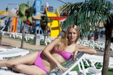 aquapark: woman lying on white chaise lounges at aquapark