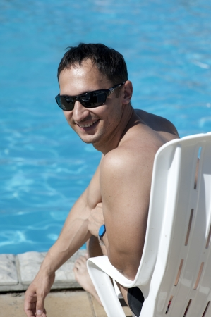 Young man in sun glasses sitting at white plastic chair by swimming-pool Stock Photo - 14273253
