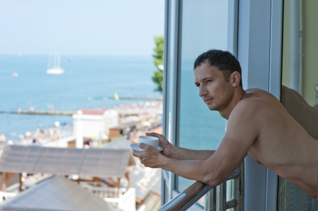 young handsome man drinking beverage on the balcony of the hotel overlooking the ocean at tropics photo