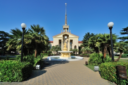 building of Commercial Sea Port of Sochi (Russia), fountain and beautiful tropical garden with palm trees photo