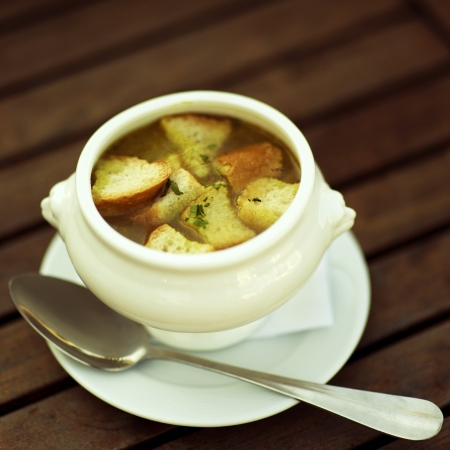 french cuisine: french onion gratin soup at wooden table Stock Photo