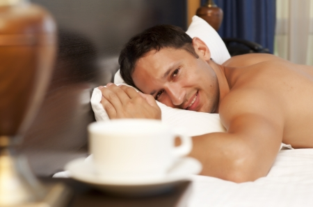 man sleeping on a bed, a cup of tea on the bedside table and lamp photo
