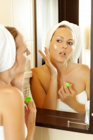 young beautiful woman applying lotion to her face  photo