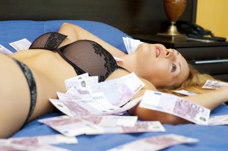 banconote euro: Giovane donna sexy posa su un letto di denaro - banconote di 500 (cinquecento) euro Archivio Fotografico