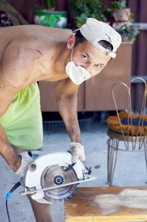 Young dirty man working at his garden with Electrical saw with circular blade for wood photo
