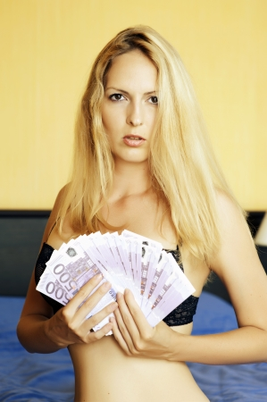 Young sexy blond  woman holding fan of five hundred euro cash Stock Photo - 14349692