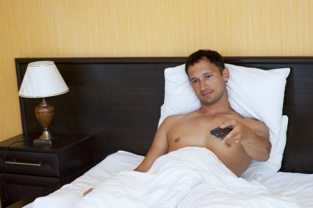 Handsome young man watching television while relaxing in bed room  photo