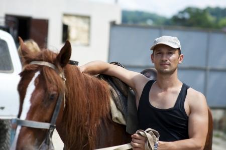 Jonge man met bruin paard buiten