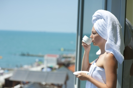 Young woman drink coffe on a hotel balcony photo