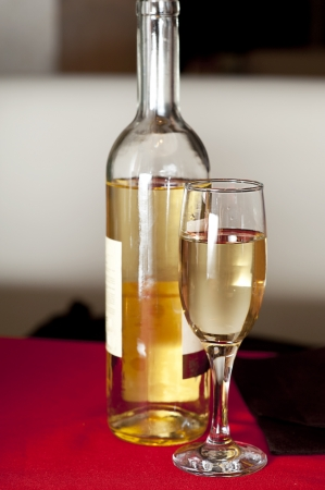 Bottle and glass of white wine at restaurant table photo