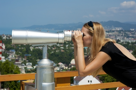 Woman on vacation looking through binoculars at the seascape photo
