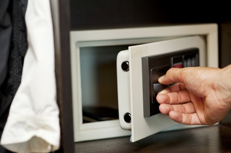 Mens hand opens a safe hidden in the wardrobe. Small home or hotel safe Stock Photo