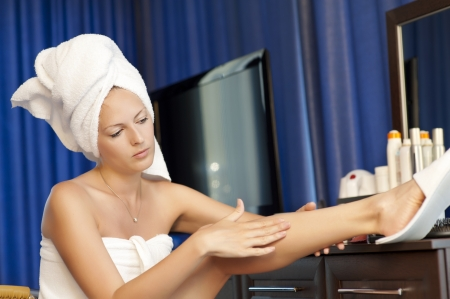 Young woman with cosmetic lotion in a bedroom. Concept body care. She is applying moisturizer cream on her slim legs