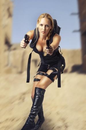 Sexy beautiful dangerous woman shooting from two hand guns Stock Photo - 14379211