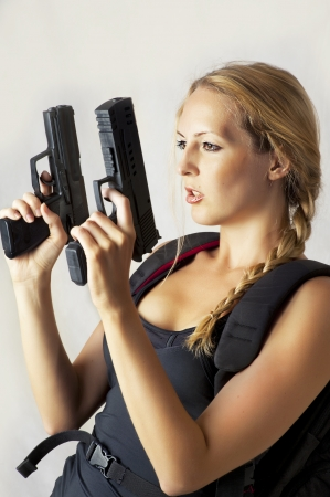 Sexy beautiful dangerous woman shooting from two hand guns Stock Photo - 14379215
