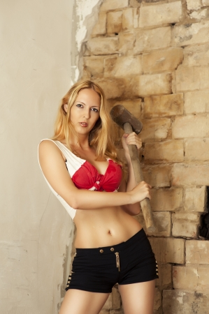 Sexy blonde with big metal hammer with a wooden handle photo