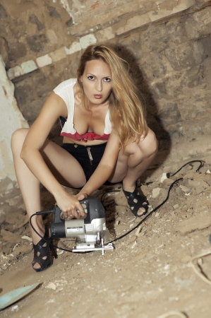 sexy construction worker: Young sexy female model builder using a jigsaw