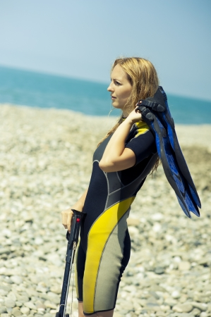 wetsuit: Woman Freediver in a diving suit an underwater pneumatic gun  Stock Photo