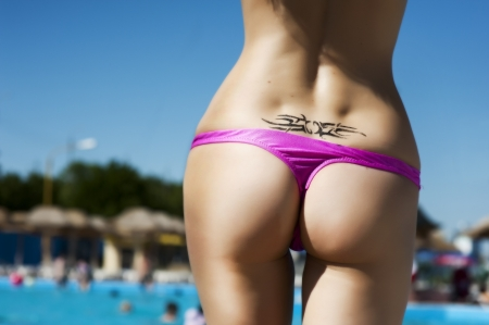 nude female buttocks: Sexy female buttocks in pink bikini on tropical  beach and temporary tattoos on back