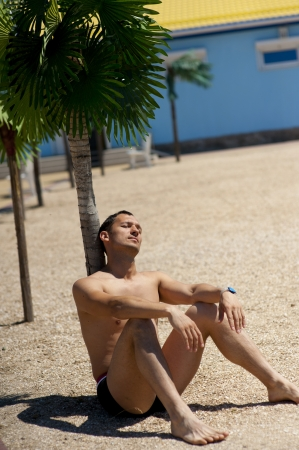 Young sexy man sitting and relaxing about palm tree on tropical resort Stock Photo - 14426033