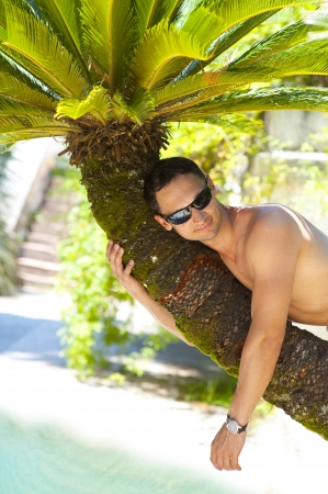 Fashion man lying upon palm tree on the beach  photo