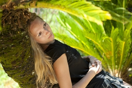 Young woman lying on a palm tree on a tropical resort Stock Photo - 14426029