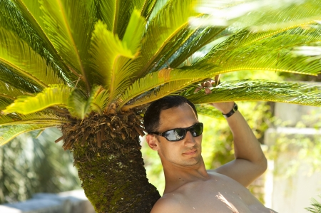 Young sexy man sitting and relaxing about palm tree on tropical resort Stock Photo - 14426035