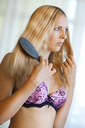 Young sexy blond woman in pink lingerie combing her hair Stock Photo
