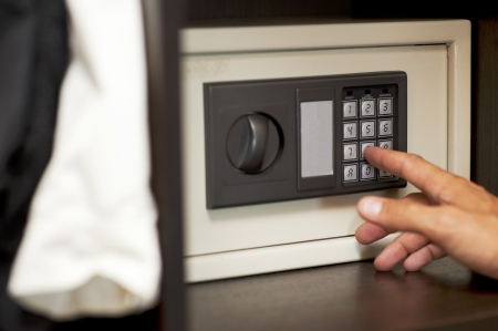 Male hand gaining an electronic code to the locked safe photo