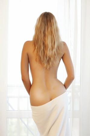 portrait of a beautiful and sexy young woman, standing about window with a bare back