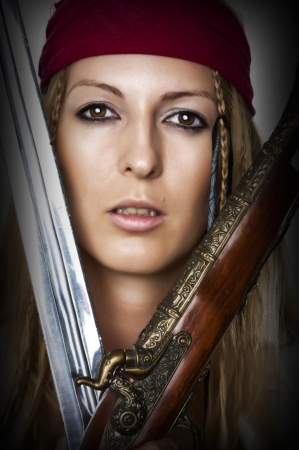 Close up portrait of female pirate with blade of sword and old hand gun photo