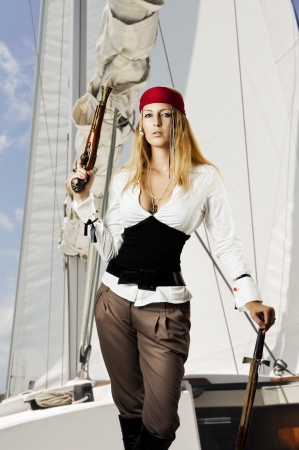 Sexy young woman pirat on the schooner holding a flintlock pistil and medieval sword in a pirates outfit  Stock Photo - 14426065