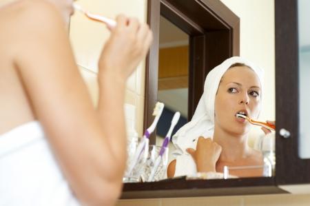 Woman in white towels bathroom brushing teeth  photo