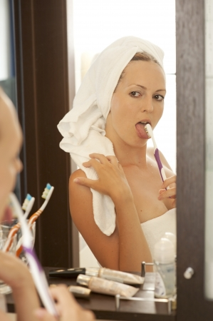 Woman in white towels bathroom brushing teeth and tongue photo