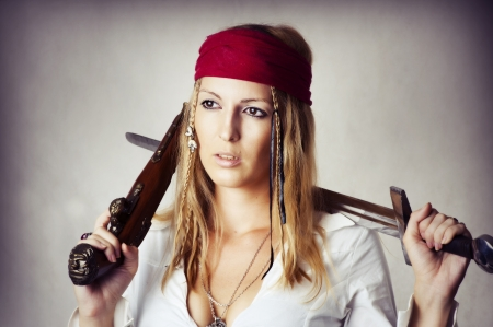 Fashion portrait of young sexy blond woman in pirat style with old handgun and medieval sword photo