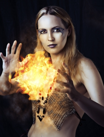Portrait of dangerous woman witch with fire ball and dark make up