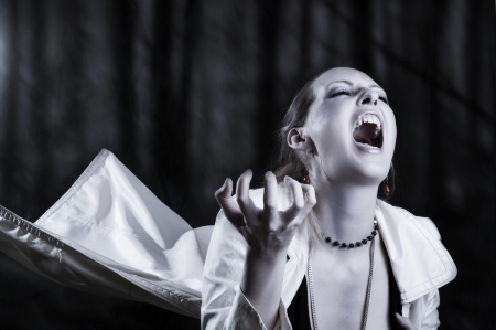 Portrait of  young woman screaming  - vampire style for halloween photo