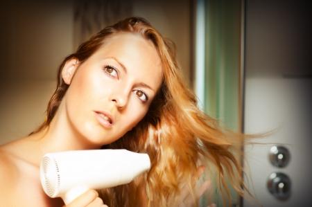 Beautiful blonde woman drying her hair  photo