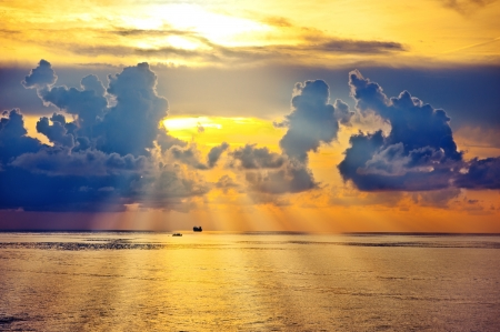 Beautiful sunrise on sea or ocean with ships on horizon and clouds photo