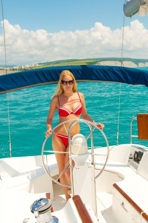 Young sexual fit woman in bikini - captain of sail boat at cruise in tropics