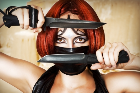 knifes: Fantasy style - red haired woman with dark creative make up, mask on her face and two combat knifes